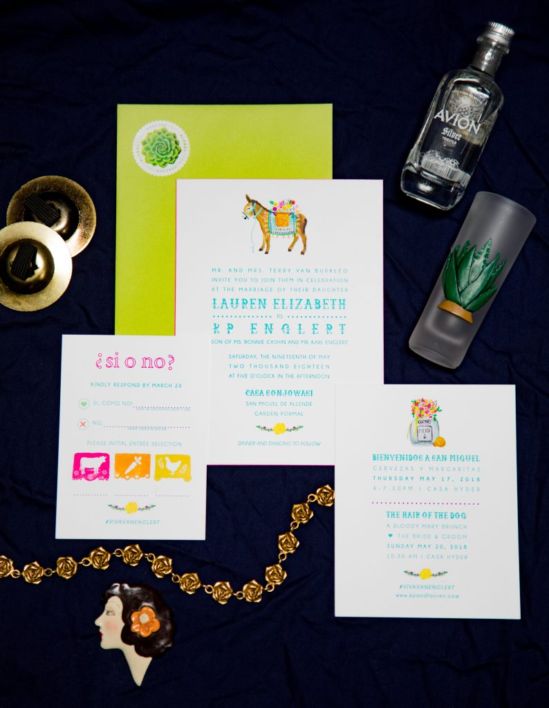 Flat lay of a letterpress wedding invitation suite for a destination wedding in San Miguel Allende. The playful design features watercolor illustrations of papel picado, a burro / donkey, and a colorful bouquet in a tequila bottle. The envelope is lime green with a succulent stamp, and the invitation has pink edge painting.