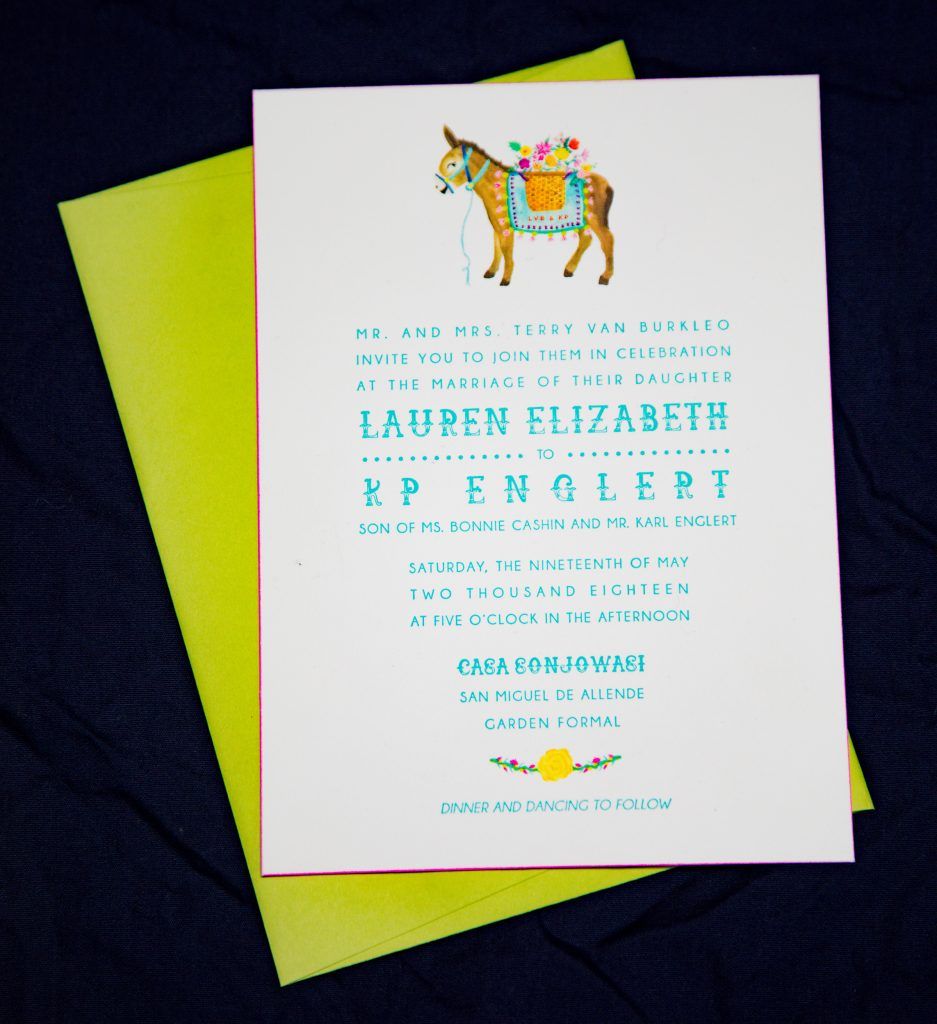 Letterpress wedding invitation with watercolor illustration of a burro / donkey carrying flowers and a floral garland with a yellow flower. Text is light blue, and design is playful. The invitation has pink edge painting.