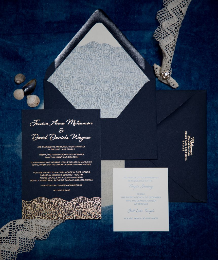 Flat lay of a wedding invitatin printed in gold foil on navy paper, with a digitally printed envelope liner featuring the Japanese wave pattern Seigaiha