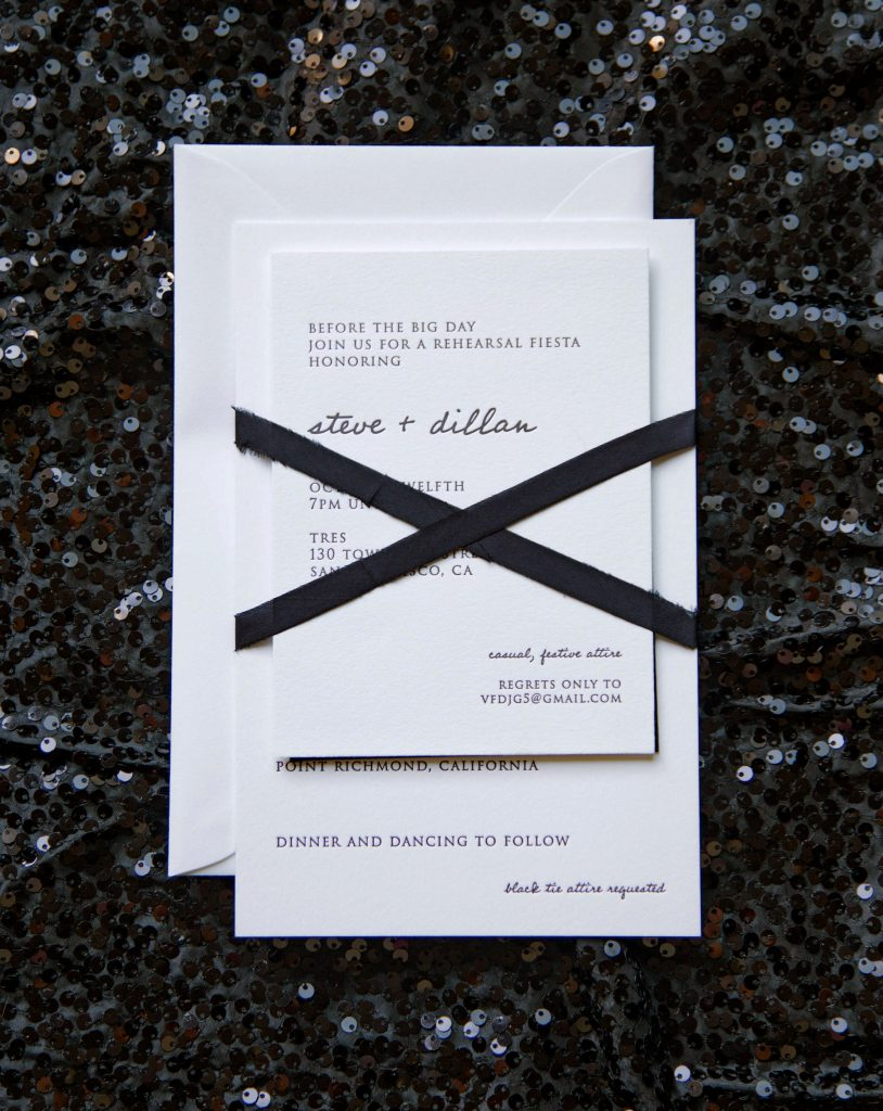 Photo of an assembled letterpress wedding invitation suite wrapped in black silk ribbon with modern, casual hand lettering and traditional block type
