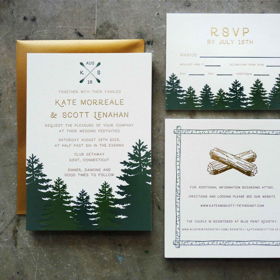 A wedding invitation suite with rich green redwood trees, modern sans serif font in gold, unique sailing monogram with oars, and camping themed details card with campfire logs foilstamped in gold