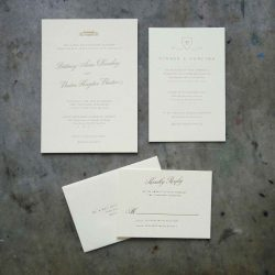 Traditional wedding invitation with copperplate calligraphy letterpress printed in gold on cream stock with formal serif font. Black tie.