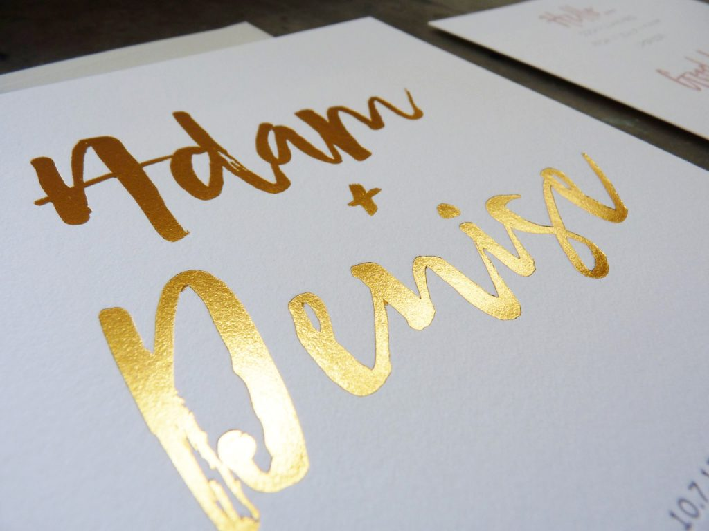 Close up of gold foil printing on a letterpress wedding invitation. Photo shows the way the light plays off the metallic gold foil. Gray letterpress print is barely visible in the bottom corner of the photo.