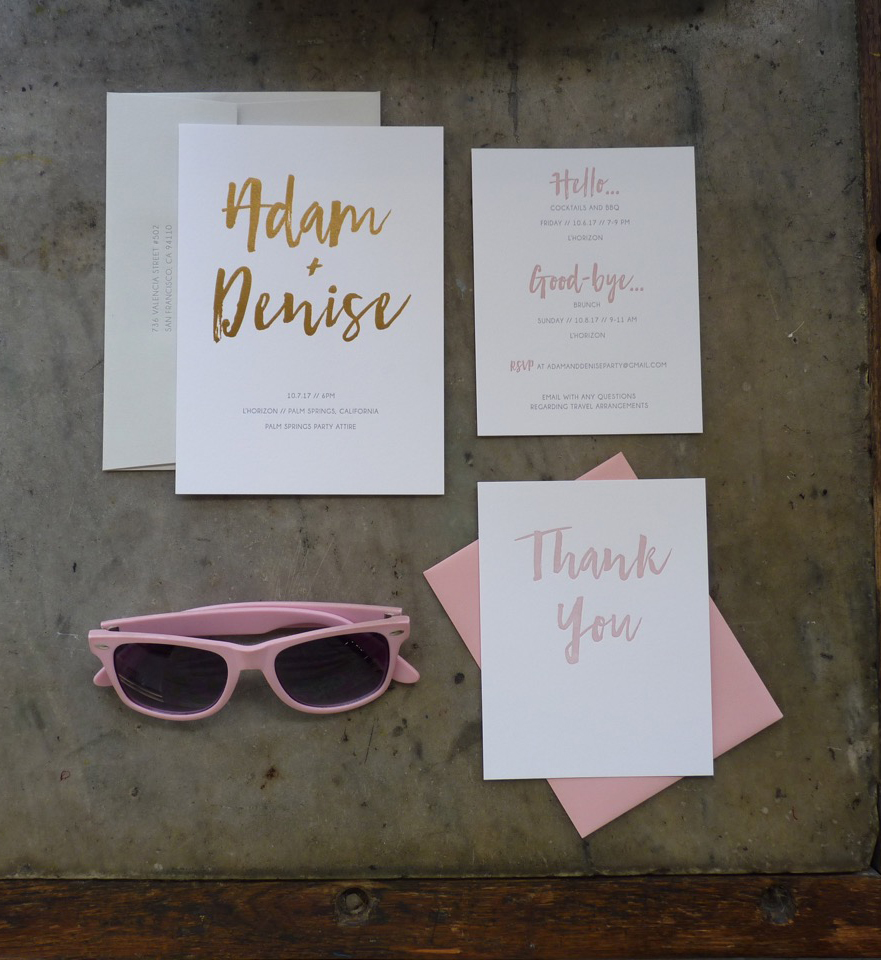Letterpress and gold foil wedding invitation suite featuring oversized modern brush lettering / calligraphy in gold foil and blush ink, and gray sans serif type. Pink envelope. Arranged in a flat lay with pink sunglasses.