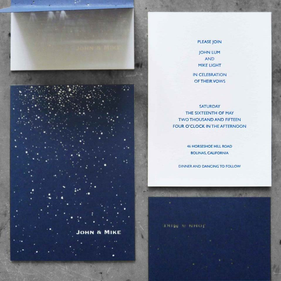 A wedding invitation suite with blue ink on white paper, white foil on navy blue paper, and die-cut stars on a folded thank-you card that let the light through.