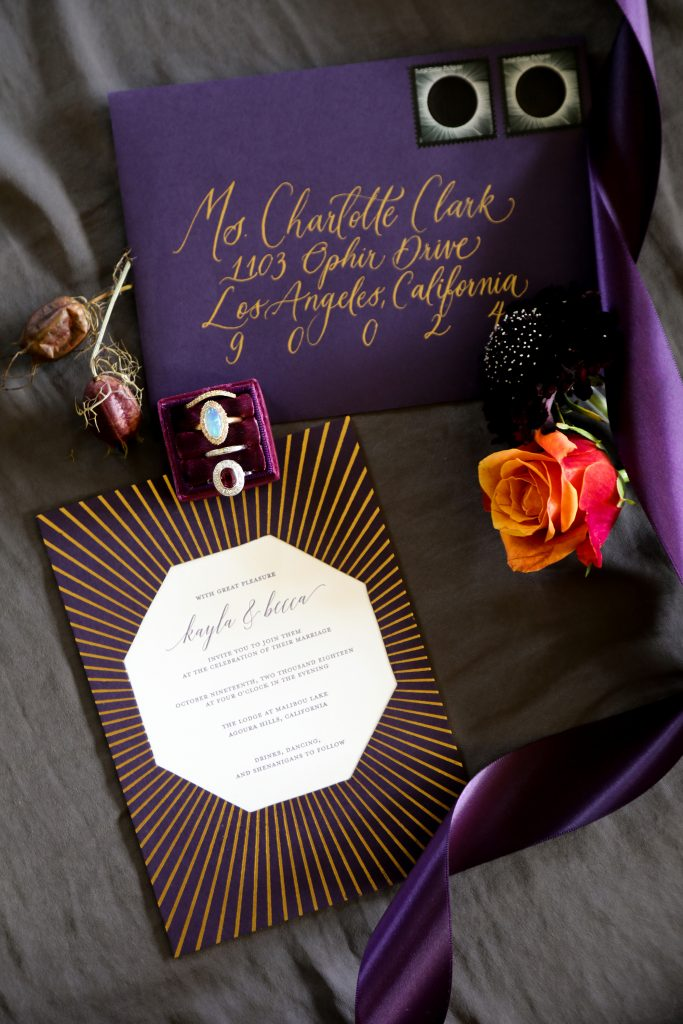 A wedding invitation featuring gold foil in a sunburst pattern, gold calligraphy, deep plum paper, and stamps with the lunar eclipse. The invitation is surrounded by a purple ribbon, orange rose, dried poppy pods and a moonstone ring.