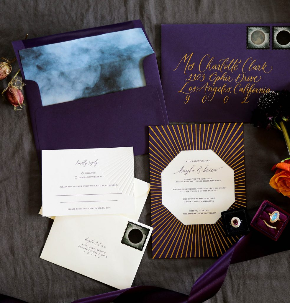 Wedding invitation with gold foil sunburst, plum paper, plum letterpress and blind deboss RSVP, gold calligraphy on plum envelope, and smoke envelope liner